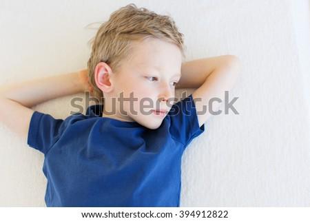 beautiful upset boy lying and looking away - stock photo