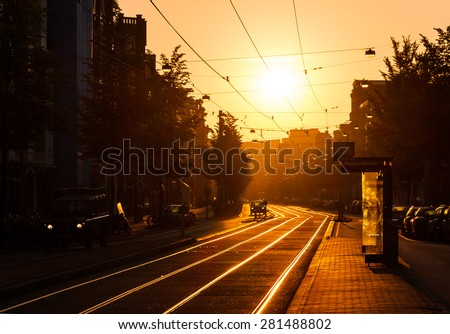 Beautiful urban sunrise in the city of Amsterdam, the Netherlands, at the tram stop - stock photo