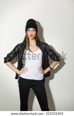Beautiful urban trendy teenage girl in white shirt, black leather jacket, black beanie hat and jeans pouting posing looking at camera with hands on hips. White background, vertical, mild retouch. - stock photo