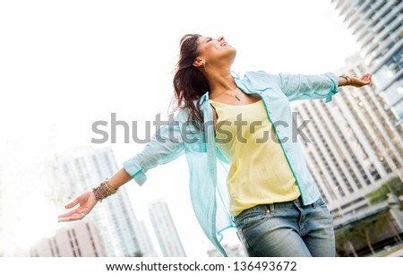Beautiful urban woman enjoying her freedom with arms open - stock photo