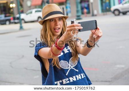 Beautiful urban woman taken picture of herself, selfie - stock photo