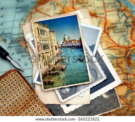 Beautiful vacation photograph from  from the Grand Canal of Venice with the famous landmark cathedral Santa Maria della Salute laying on a desk with several images and a journal with pencil - stock photo