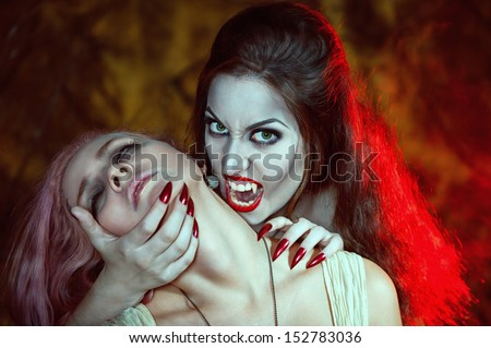 Beautiful vampire woman and her victim  - stock photo