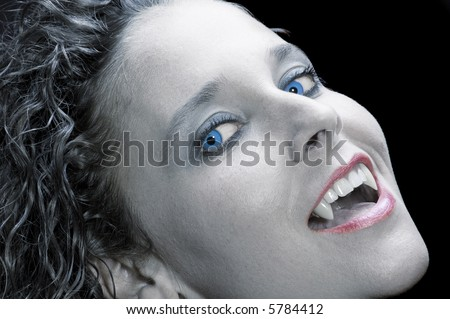 Beautiful vampiress on black background - stock photo