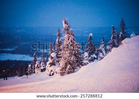 Beautiful vibrant night scandinavian winter aerial landscape with slopes, skiing resort and cottages with lights - stock photo