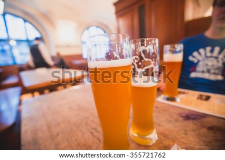 Beautiful vibrant picture of gold coloured beer glasses assortment, on wooden table, a summer sunny day, german unfiltered wheat beer - stock photo