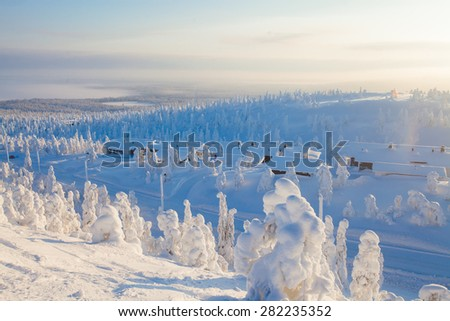 Beautiful vibrant scandinavian winter aerial landscape with slopes, skiing resort and cottages with lights - stock photo