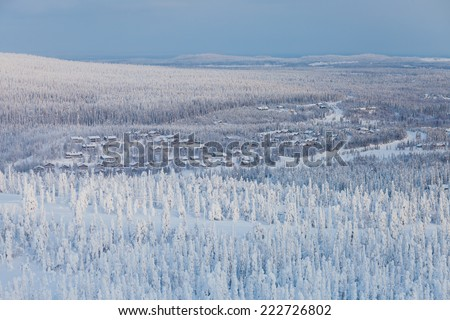Beautiful vibrant sunny scandinavian lapland winter aerial landscape with slopes, skiing resort and cottages - stock photo