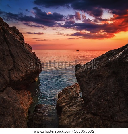 Beautiful vibrant sunset at the summer sea. Textured rocks in the foreground and fishermen in a boat. Ideal as a photo for interior decoration. - stock photo
