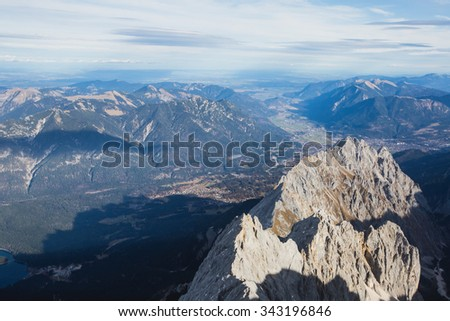 Beautiful vibrant view on mountain Zugspitze (highest mountain of Germany) with mountain lake in foreground, landscape of Alpine Alps mountain view from Zugspitze, top peak of Germany  - stock photo