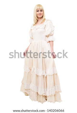 Beautiful Victorian Lady standing in sideway in white background. Beige Dress with flowers, Ruffles and Lace. Long fair straight Hair. Looking at the Camera. - stock photo