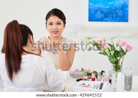 Beautiful Vietnamese girl enjoying manicure process in beauty salon - stock photo