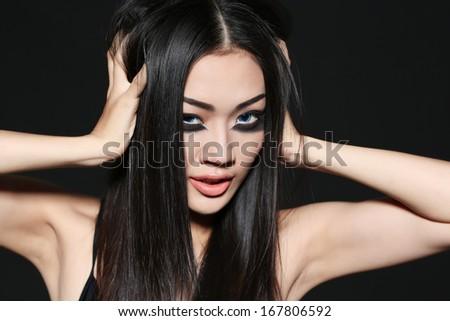 Beautiful Vietnamese girl with black mascara under eyes - stock photo