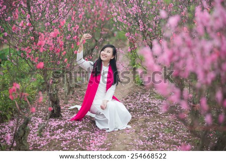 Beautiful Vietnamese girl with traditional dress (ao dai) is in peach flower garden in Hanoi, Vietnam