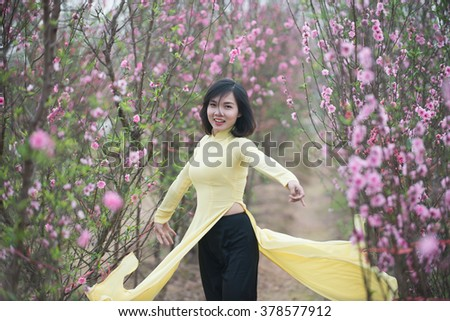 Beautiful Vietnamese girls with traditional dress (ao dai) is in peach flower garden in Hanoi, Vietnam