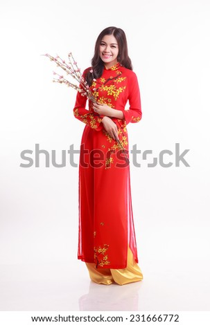 Beautiful Vietnamese woman with red ao dai  holding cherry blossom for celebrate lunar new year on white background - stock photo