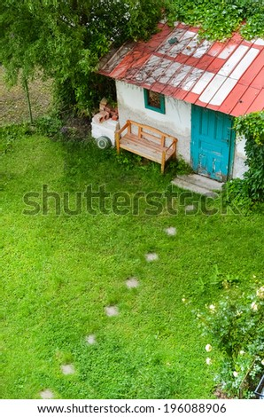 Beautiful view in peaceful green garden with garden house - stock photo