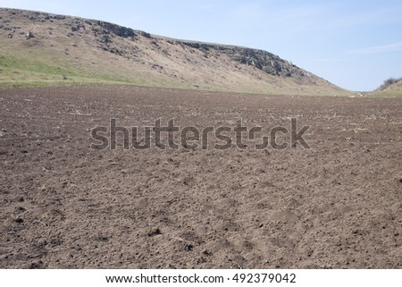Beautiful view of a field with hills and blue sky as a background.
