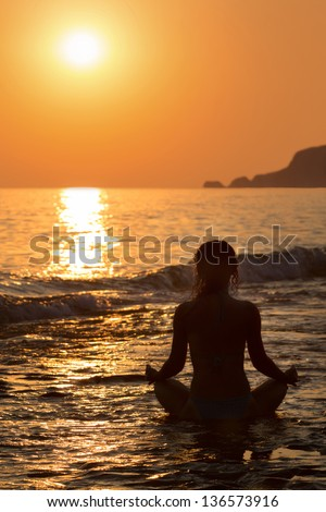 Beautiful view of a girl sitting in a yoga pose on the beach at sunset