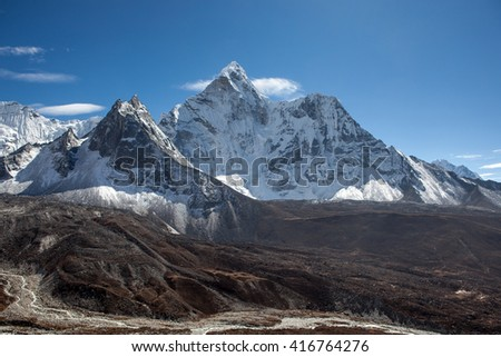 Beautiful view of Ama Dablam mountain range on the famous Everest Base Camp trek in Himalayas, Nepal. Snowy mountain range on a bright sunny day. Panoramic mountain range landscape. - stock photo