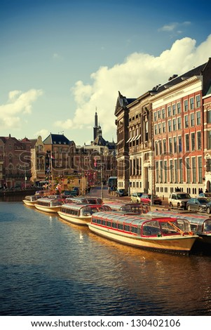 Beautiful view of Amsterdam canals with a boat. Urban scene - stock photo