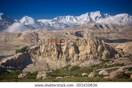 Beautiful view of buddhist monastery on the rocky hills with snowy mountains on the background.  Nepal, Upper Mustang restricted area, Namgyal monastery (3,950 m).