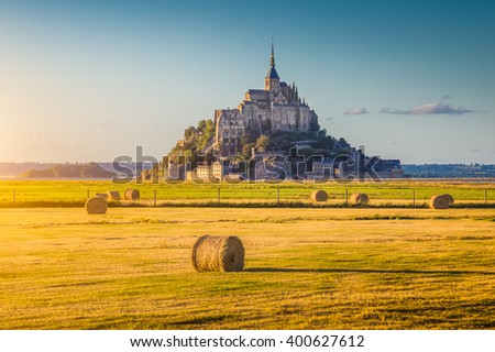 Beautiful view of famous historic Le Mont Saint-Michel tidal island in beautiful golden evening light at sunset in summer with hay bales on empty fields, Normandy, northern France - stock photo