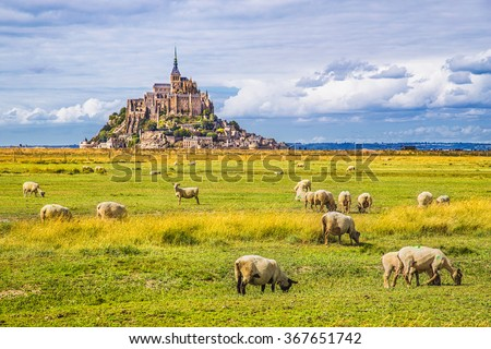Beautiful view of famous historic Le Mont Saint-Michel tidal island with sheep grazing on fields of fresh green grass on a sunny day with blue sky and clouds in summer, Normandy, northern France - stock photo