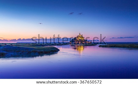 Beautiful view of famous Le Mont Saint-Michel historic tidal island in beautiful twilight during blue hour at dusk, Normandy, northern France - stock photo