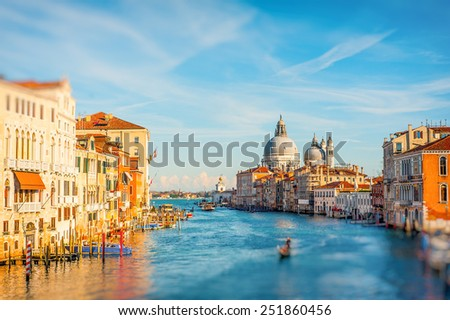 Beautiful view of famous tourist destination on a sunny day with colorful houses and with the Santa Maria Della Salute church on Grand Canal, Venice, Italy - stock photo