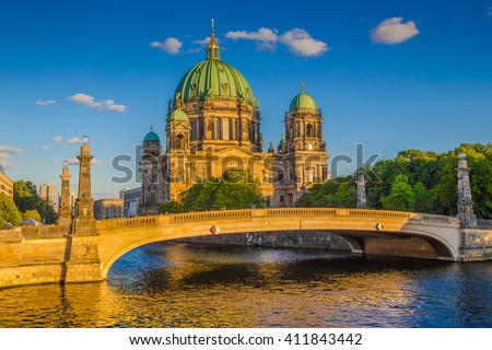 Beautiful view of historic Berlin Cathedral (Berliner Dom) at Museumsinsel (Museum Island) with famous Friedrichsbrucke over Spree river in golden evening light at sunset in summer, Berlin, Germany - stock photo