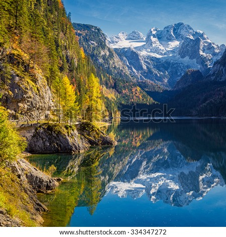 Beautiful view of idyllic colorful autumn scenery with Dachstein mountain summit reflecting in crystal clear Gosausee mountain lake in fall, Salzkammergut region, Upper Austria, Austria - stock photo