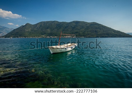 Beautiful view of Kotor bay with moored white wooden rowboat - stock photo