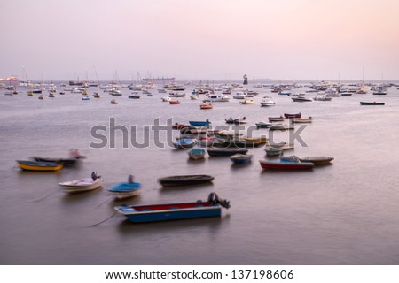 Beautiful view of many boats in the waves at twilight in Mumbai, India. Long exposure shot. - stock photo
