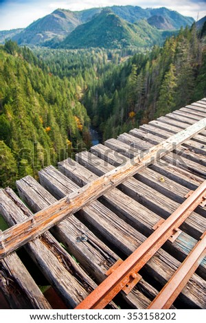 Beautiful view of mountains and green forest from the wood railway bridge in Washington - stock photo
