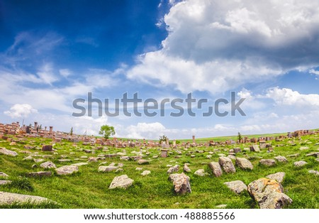 Beautiful view of old stones on lawn against of magnificent blue cloudy sky