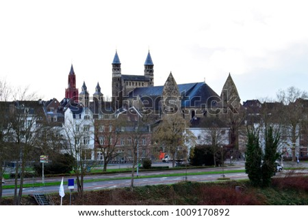 Beautiful view of Onze Lieve Vrouwe (Basilica of Our Lady), very olden history and building or house near the road in the old city center in Maastricht, Netherlands. Travel style and holidays concept.