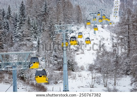 Beautiful view of row of yellow ski lift cabins in alps - stock photo