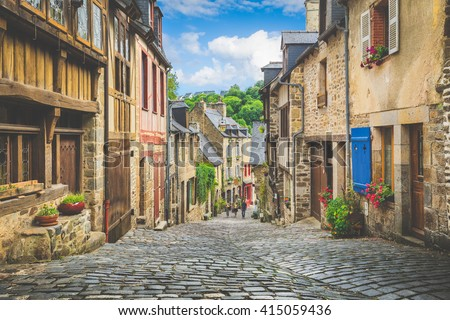 Beautiful view of scenic narrow alley with historic traditional houses and cobbled street in an old town in Europe with blue sky and clouds in summer with retro vintage Instagram grunge filter effect - stock photo