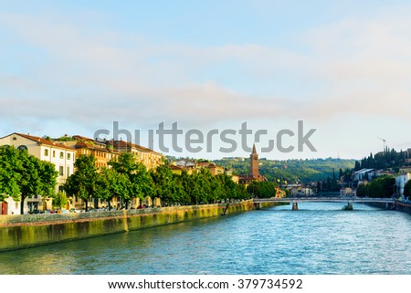 Beautiful view of the Adige River and the Ponte Nuovo (New Bridge) in Verona, Italy. Verona is a popular tourist destination of Europe. - stock photo