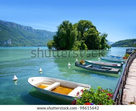 Beautiful view of the Annecy Lake in French Alps, a summer day with boats in the foreground. Annecy. Haute Savoie. French Alps. France. - stock photo