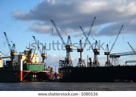 Beautiful view of the cranes and logistics at the harbour of Hamburg with blue sky (close-up) - stock photo