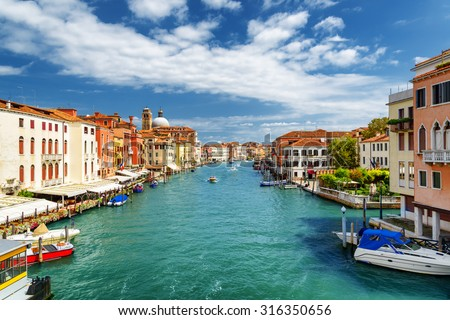 Beautiful view of the Grand Canal with boats from the Ponte degli Scalzi in Venice, Italy. Colorful facades of old houses on waterfront. Venice is a popular tourist destination of Europe. - stock photo