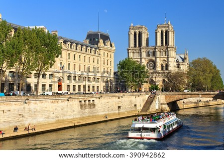 Beautiful view of the river Seine with a canal-boat and the Notre-Dame Cathedral in Paris  - stock photo