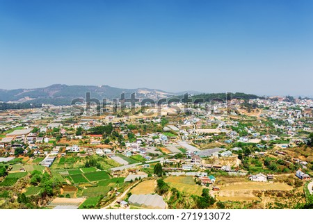 Beautiful view of the valley of agricultural lands and Da Lat city (Dalat) on the blue sky background in Vietnam. Da Lat is a popular tourist destination of Asia. - stock photo