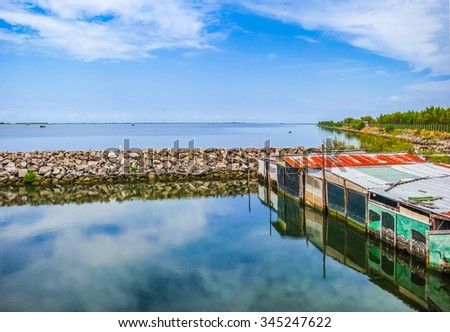 Beautiful view of tranquil seascape with colorful shanties in the Delta del Po national park region on a sunny day, Venetian Lagoon, Adriatic Sea, Italy - stock photo