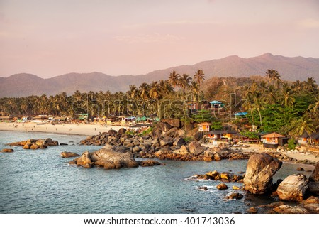 Beautiful view of tropical sunset beach with bungalow and coconut palm trees at Palolem in Goa, India  - stock photo