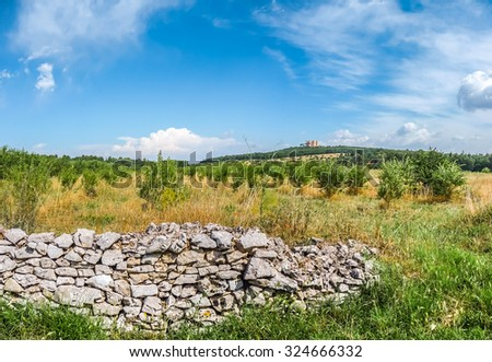 Beautiful view of typical landscape in Apulia with historic stonewall and famous Castel del Monte in the background, southeast Italy - stock photo