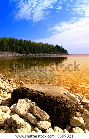 Beautiful view on a rocky shore with clear water and golden reflections. Georgian Bay, Canada. - stock photo