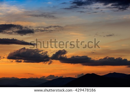 Beautiful view on clouds over mountains silhouette in evening